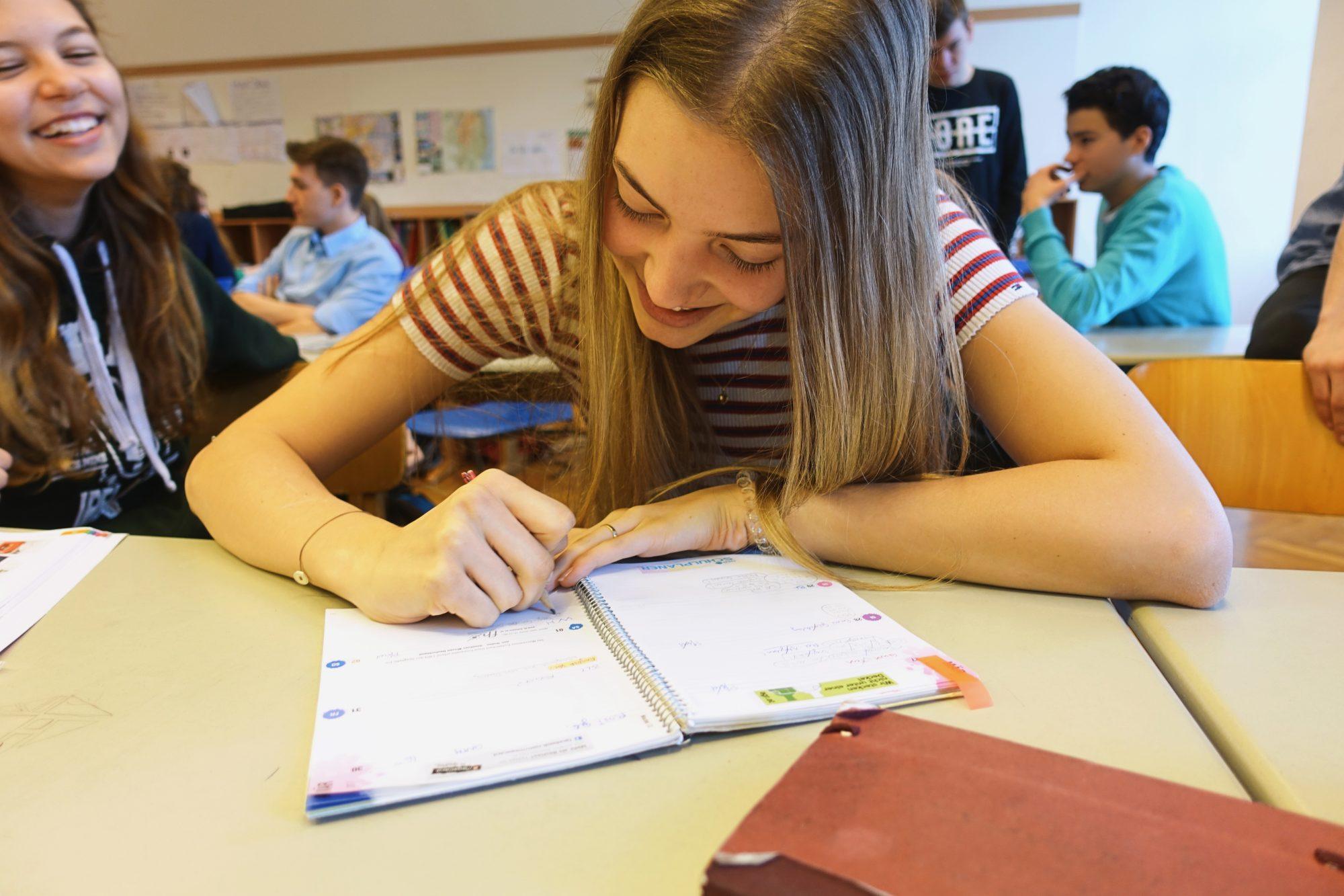 AHS-Schülerin Laura notiert ein paar Zeilen in ihrem Schulplaner.